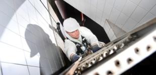 Mann steigt in den unterirdischen Wasserbehälter im Schutzsanzug ab.
